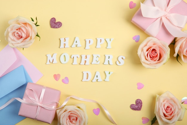Happy mother's day text with roses and gifts on yellow background
