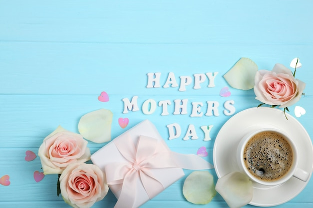 Happy mother's day text with roses, hearts and gifts on blue background