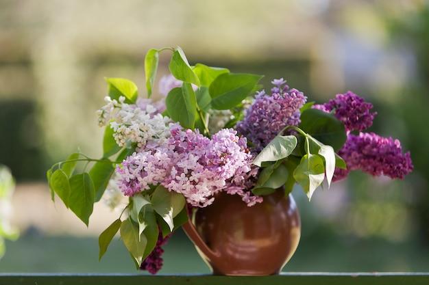 Счастливый день матери с цветущей сиренью ветви в вазе на зеленом столе.