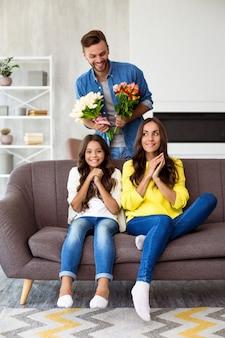С днем матери или женщины. взволнованная и милая семья празднует женский день. муж приготовил сюрприз жене и маленькой симпатичной дочке