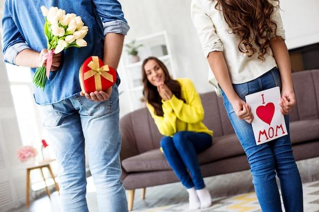 С днем матери или женщины. взволнованная и милая семья празднует женский день. муж приготовил жене сюрприз
