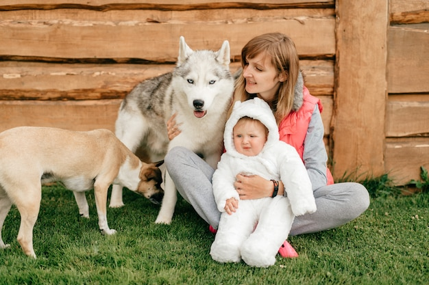 Happy mother sitting on grass and holding funny baby bear costume together with two beautiful dogs