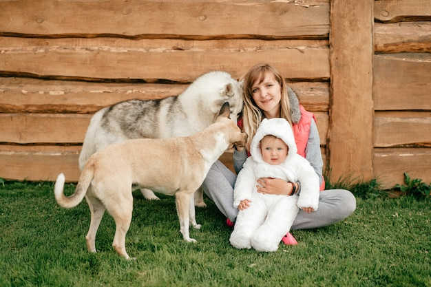 Happy mother sitting on grass and holding funny baby boy in reddy bear costume together with two beautiful dogs.