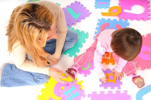 Счастливая мать, сидя на полу со своей маленькой дочерью и изучая числа над белой стеной. концепция образа жизни красивых счастливых детей