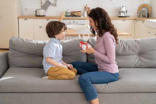 Happy mother sitting on sofa at home congratulating her kid