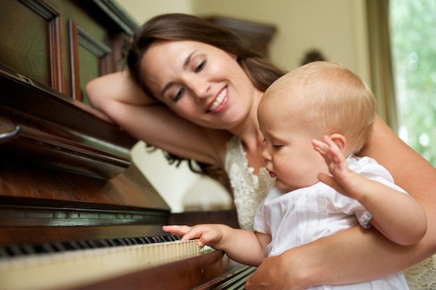Happy mother smiling as baby plays piano