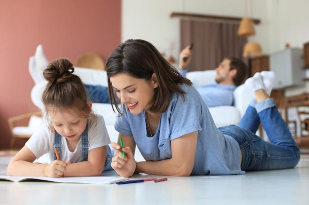 暖かい床に横たわって創造的な活動を楽しんでいる幸せな母親の微笑む娘、アルバムに絵を描く鉛筆を描く、ソファで休んでいる父親、家族は一緒に自由な時間を過ごします。