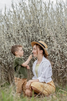 Happy mother and son having fun together. mother gently hugs her son. in the background white flowers bloom. mother's day.