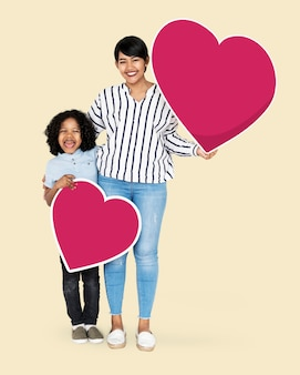 Happy mother and son holding heart icons