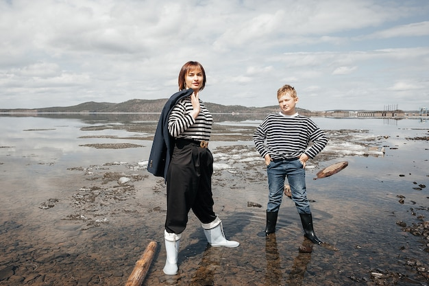 Happy mother and son on the river bank stand on logs in striped vests.