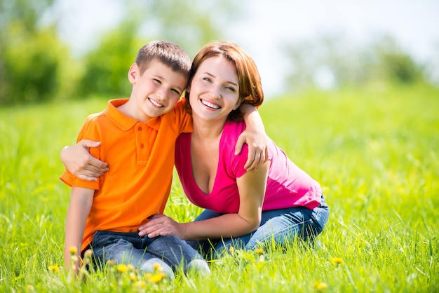 Happy mother and son in the spring meadow outdoor portrait