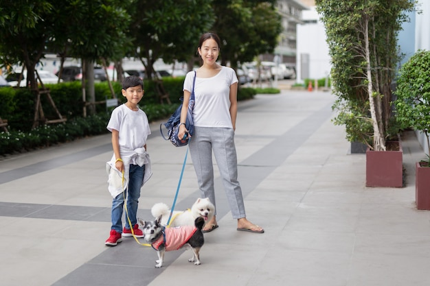 Happy mother and son walking with dogs outside the building.