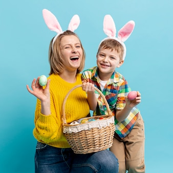 Happy mother and son with painted eggs in basket