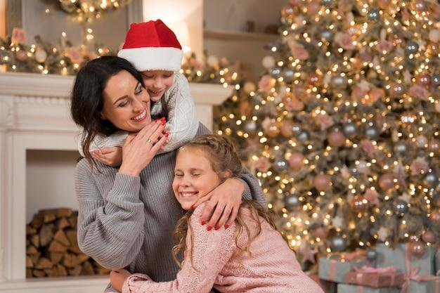 Счастливая мать проводит время со своими детьми на рождество
