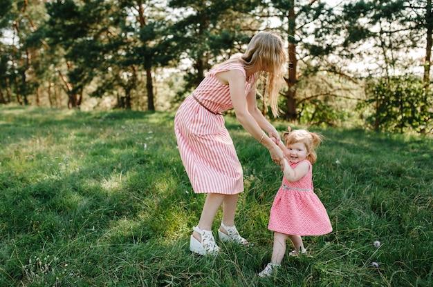 Счастливая мать раскручивает дочь на руках на природе на летних каникулах. мама и девочка играют в парке во время заката. понятие дружной семьи. Premium Фотографии