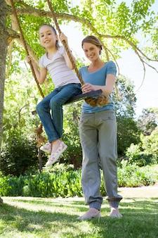 公園で幸せな母親を揺らす娘
