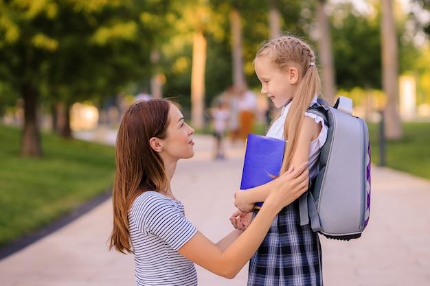 Счастливая мать берет маленькую дочь школьницу в школу