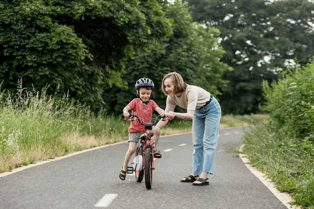 Счастливая мать учит ребенка-сына кататься на велосипеде по велосипедной дорожке