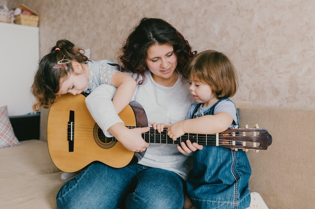 A happy mother teaches her two young daughters to play the acoustic guitar.