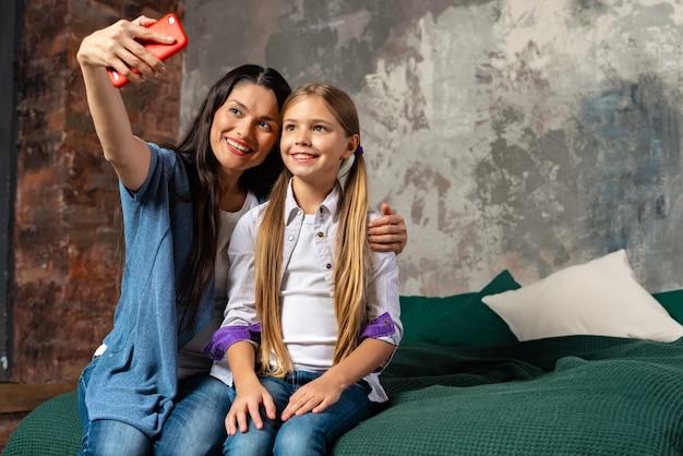 Happy mother tender hugs her pretty daughter. doing selfie