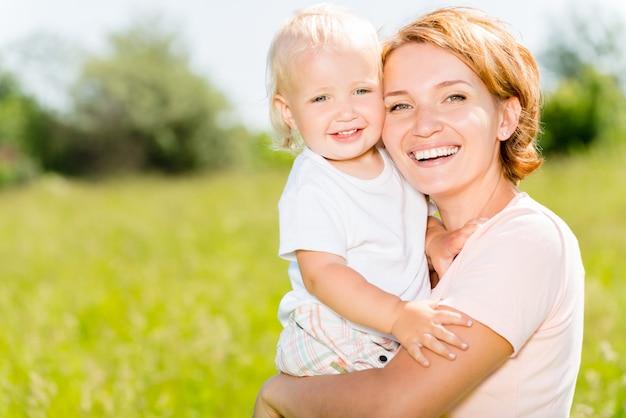 Madre felice e figlio del bambino nel ritratto all'aperto del prato di primavera