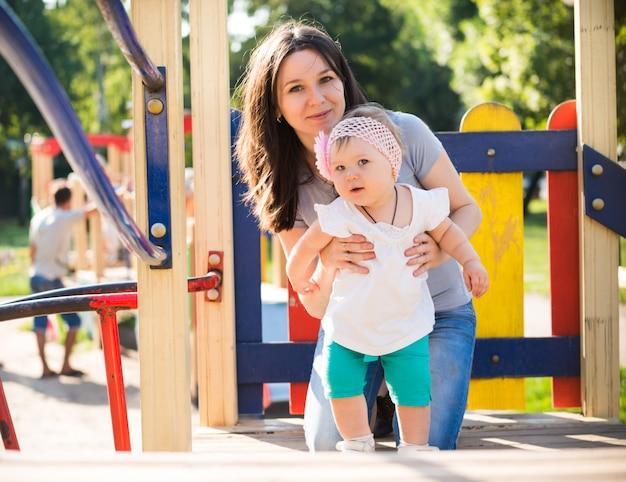 Счастливая мать гуляет и играет со своей маленькой дочерью