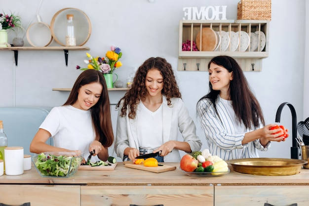 Happy mother washing vegetables and her daughters together in a kitchen are preparing a salad