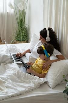 행복한 어머니는 침대에 누워 취학 전 아이를 껴안는 웹 디자인의 온라인 비디오 과정을 봅니다.
