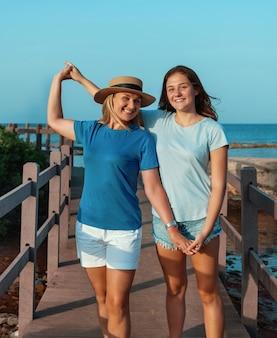 Счастливая мать в соломенной шляпе и дочь-подросток стоя у моря, держась за руки и улыбаясь