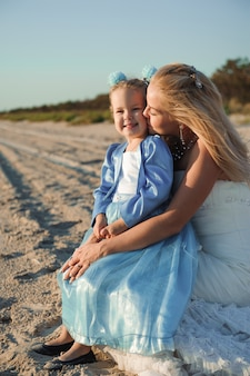 Happy mother in the wedding dress with her daughter on the beach.