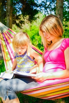 공원에서 성경의 본질에 대한 책을 읽고 해먹에서 아기와 함께 행복한 어머니