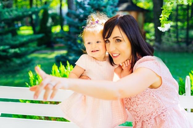 公園で自然を見て、白いベンチに座っていることに興味がある子供を持つ幸せな母 Premium写真