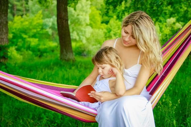 자연 공원에서 해먹에 책을 읽고 아이와 함께 행복 한 어머니