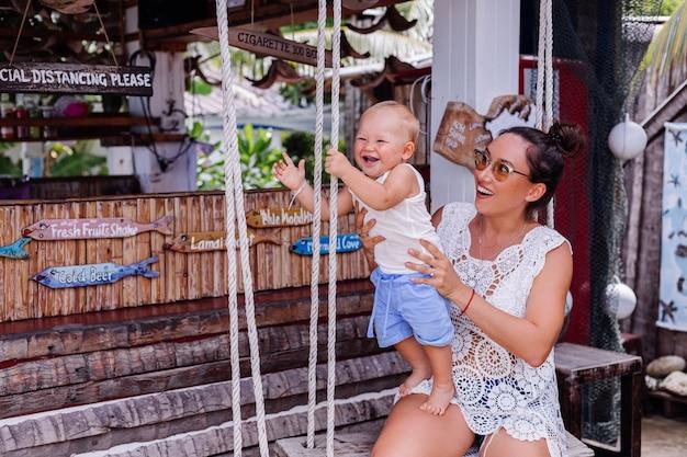Счастливая мать с мальчиком на качелях