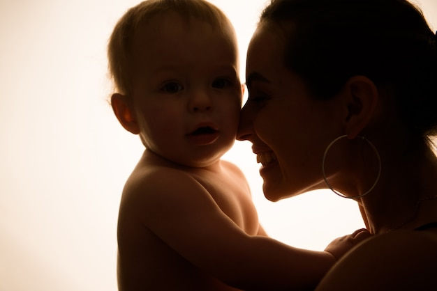 Счастливая мать с ребенком, с удовольствием вместе на фоне лайтбокс.
