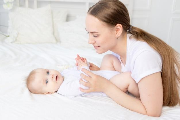 아기가 놀고 집에 있는 침대에서 부드럽게 껴안고 있는 행복한 어머니.