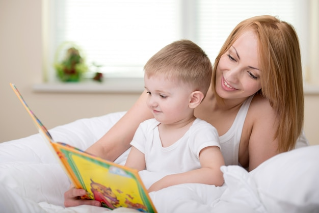 Happy mother with baby reading book together.