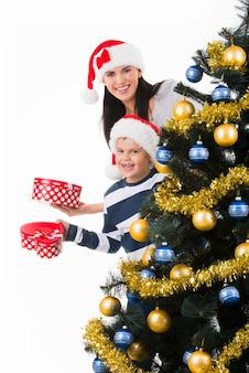 Счастливая мать с ребенком держит коробку с подарком возле елки