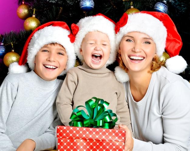 Счастливая мама с детьми держит новогодний подарок на праздник рождества - в помещении