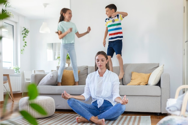 目を閉じて幸せな母親が床で蓮華座で瞑想し、興奮した子供たちがソファに飛び乗って明るく広々としたリビングルーで叫んでいる間、内側の調和を救おうとしています