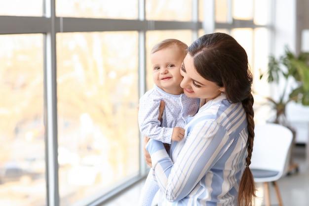 窓の近くのかわいい赤ちゃんと一緒に幸せな母