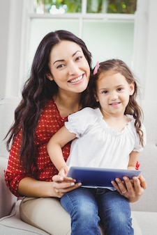 Happy mother with daughter holding a digital tablet at home