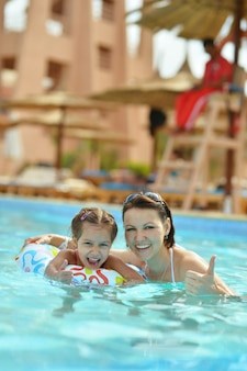 Happy mother with daughter in the pool