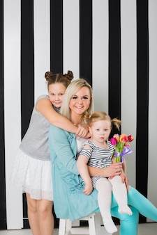 Happy mother with daughters and bouquet of flowers