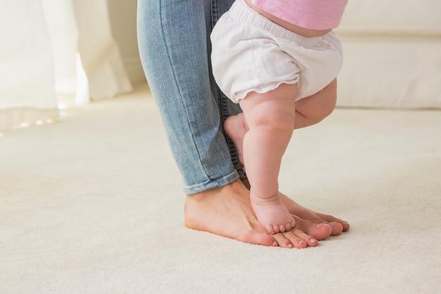 Счастливая мать со своей девочкой учится ходить