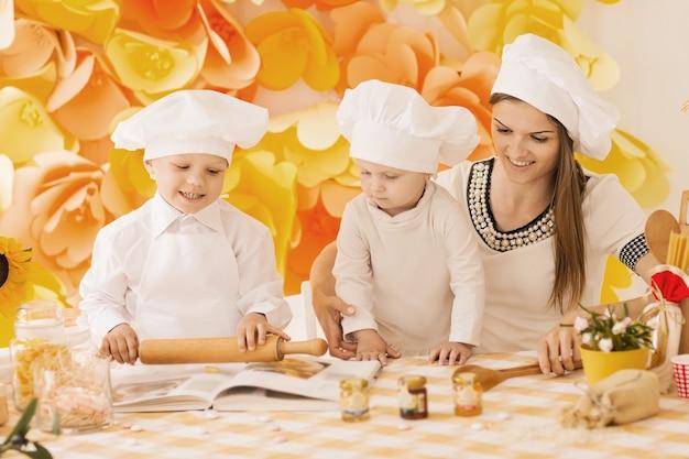 Счастливая мать с детьми, готовя ужин на кухне