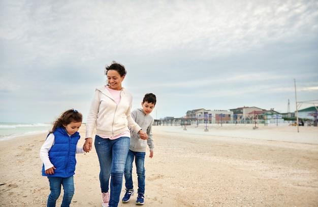 해변에서 산책 하는 그녀의 아이 들과 함께 행복 한 어머니입니다.