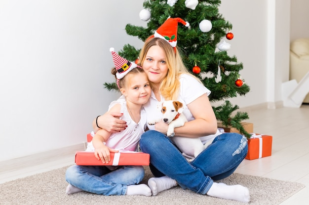 Счастливая мать с дочерью и собакой джек-рассел-терьер сидит возле елки