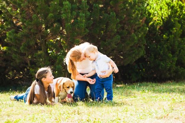 Счастливая мать с дочерью, маленьким сыном и собакой породы бигль на прогулке