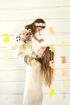 Happy mother with her daughter posing on white background with paper rabbit's shape. easter holidays.